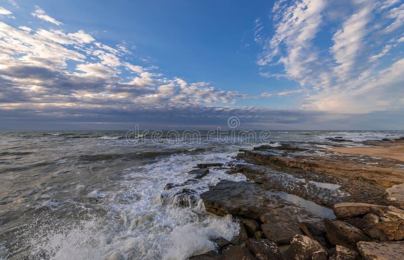 Θυελλώδης θάλασσα και δύσκολη ακτή, όμορφος δραματικός ουρανός στοκ εικόνα