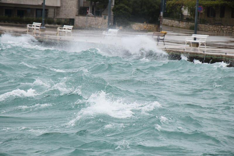 Θυελλώδης θάλασσα που καταβρέχει τα κύματα στον περίπατο ακτών με τους πάγκους σε εκτός εποχής στοκ εικόνα