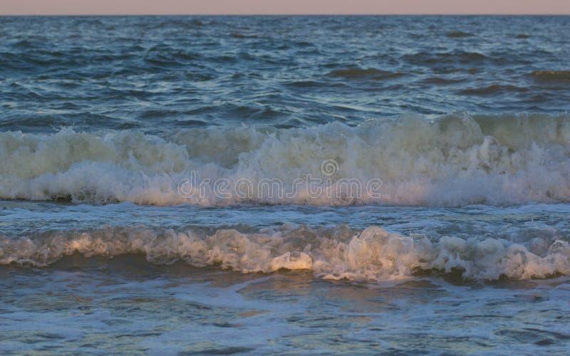 Θυελλώδες ηλιοβασίλεμα στη θάλασσα Κύμα και παφλασμός στοκ φωτογραφία