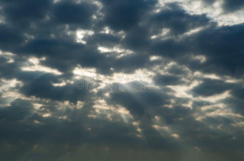Θυελλώδης σκοτεινός ουρανός με τις ακτίνες του φωτός που σπάζουν κατευθείαν στοκ εικόνα