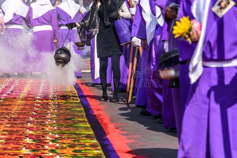 Θυμίαμα καψίματος στην πομπή Μεγάλων Παρασκευών εκτός από το βαμμένο τάπητα πριονιδιού, Αντίγκουα, Γουατεμάλα στοκ φωτογραφία