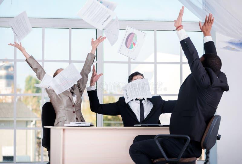 διαπραγμάτευση επιτυχής Τρεις επιτυχείς επιχειρηματίες που ρίχνουν τα έγγραφα στοκ φωτογραφία με δικαίωμα ελεύθερης χρήσης