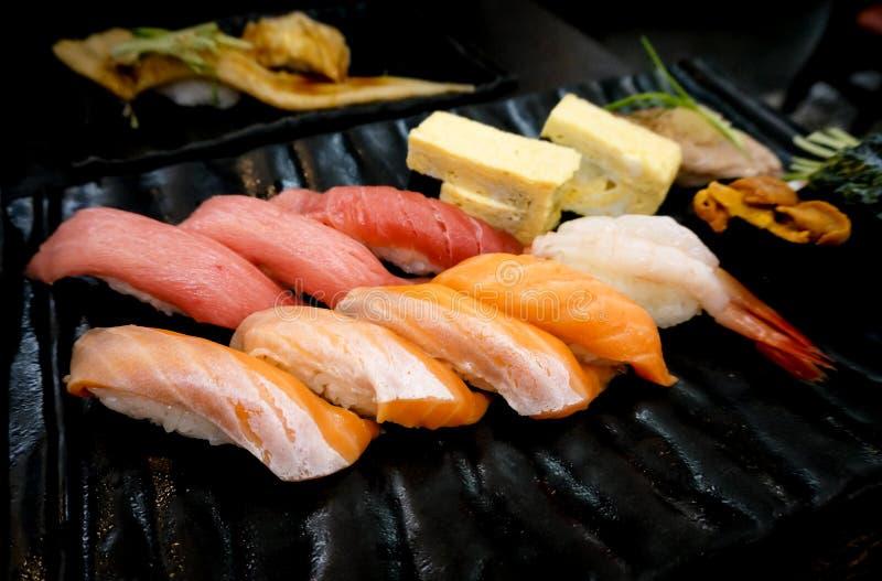 Ιαπωνικά εύγευστα σούσια ακατέργαστων ψαριών στο μαύρο πιάτο στοκ εικόνα