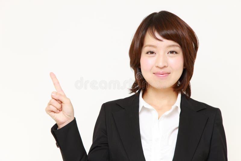 Ιαπωνική επιχειρηματίας που παρουσιάζει και που παρουσιάζει κάτι στοκ φωτογραφίες