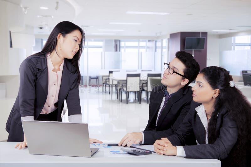 Ιαπωνική επιχειρησιακή γυναίκα που μιλά στους συναδέλφους της στοκ φωτογραφία
