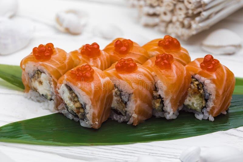 Ιαπωνική κουζίνα Σούσια που κυλιούνται σε έναν φρέσκο σολομό στοκ εικόνες με δικαίωμα ελεύθερης χρήσης