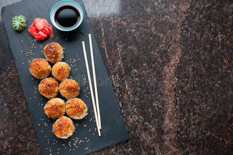 Ιαπωνική κουζίνα Ψημένα καυτά σούσια με το κρέας καβουριών και τυρί σε μια πλάκα πετρών σε ένα μαύρο υπόβαθρο γρανίτη Τοπ άποψη μ στοκ φωτογραφία με δικαίωμα ελεύθερης χρήσης