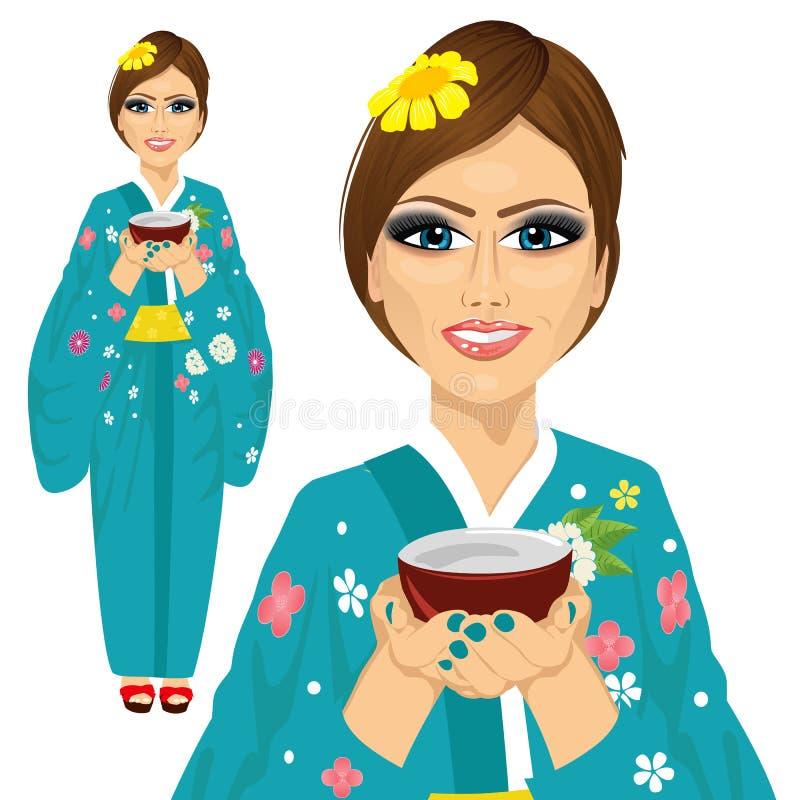 Ιαπωνική όμορφη γυναίκα που φορά το κιμονό που κρατά ένα φλυτζάνι του πράσινου τσαγιού απεικόνιση αποθεμάτων