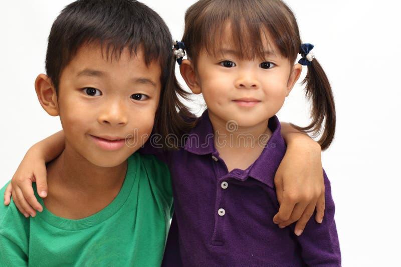 Ιαπωνικοί αδελφός και αδελφή που βάζουν τα όπλα η μια γύρω από την άλλη sholders ` s στοκ εικόνα