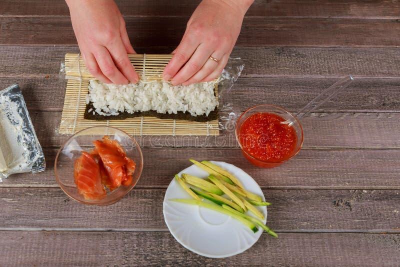 Ιαπωνικός αρχιμάγειρας που κατασκευάζει τα σούσια σολομών - ιαπωνικά τρόφιμα στοκ εικόνα με δικαίωμα ελεύθερης χρήσης