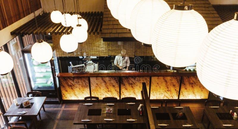 Ιαπωνικός μετρητής εστιατορίων με τον αρχιμάγειρα Βλαστός από το δεύτερο όροφο με τους λαμπτήρες στο πρώτο πλάνο στοκ εικόνα με δικαίωμα ελεύθερης χρήσης