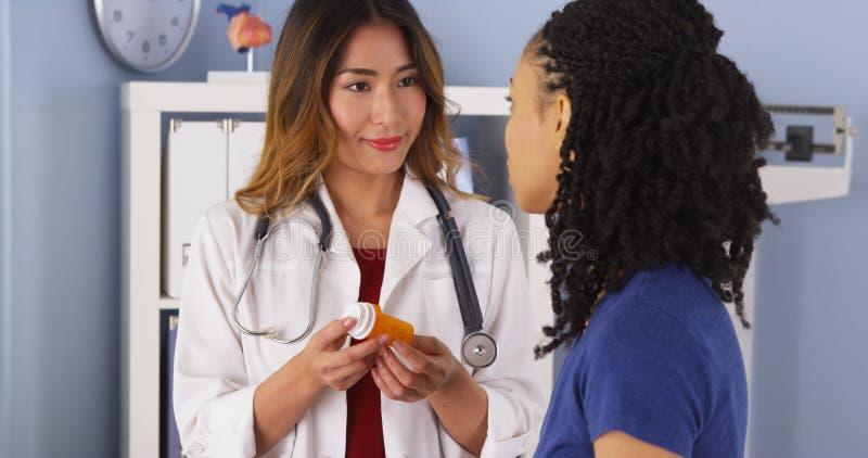 Ιαπωνικός παθολόγος που εξηγεί τη νέα συνταγή στον ασθενή αφροαμερικάνων στοκ εικόνα