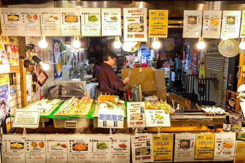 Ιαπωνικός προμηθευτής τροφίμων οδών που πωλεί ποικίλα τοπικά τρόφιμα και πρόχειρο φαγητό κατά μήκος της αγοράς τροφίμων Nishiki στοκ φωτογραφία με δικαίωμα ελεύθερης χρήσης