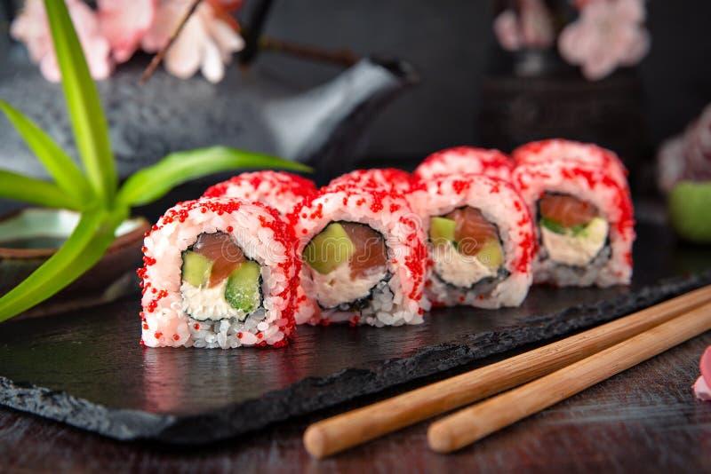 Ιαπωνικός ρόλος Καλιφόρνιας με το σολομό, αβοκάντο, αγγούρι, κρέμα με το τυρί της Φιλαδέλφειας, επιλογές σουσιών χαβιαριών tobiko στοκ εικόνες