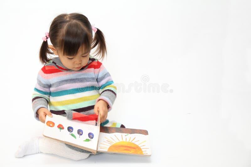 Ιαπωνικό κορίτσι που διαβάζει ένα βιβλίο εικόνων στοκ φωτογραφίες