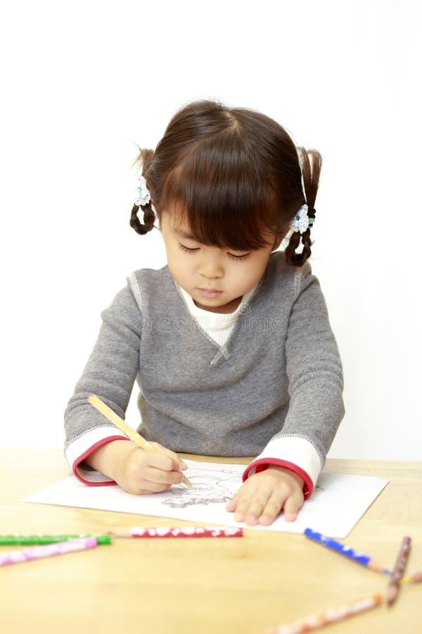 Ιαπωνικό κορίτσι που σύρει ένα χρωματίζοντας βιβλίο στοκ φωτογραφίες