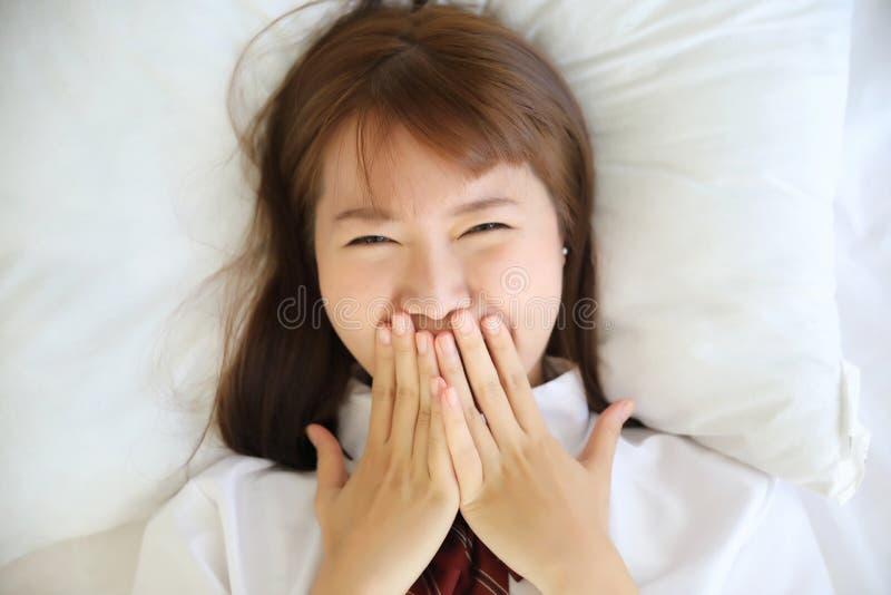 Ιαπωνικό κοστούμι σχολικών κοριτσιών πορτρέτου που χαμογελά στο άσπρο δωμάτιο κρεβατιών τόνου στοκ φωτογραφία με δικαίωμα ελεύθερης χρήσης