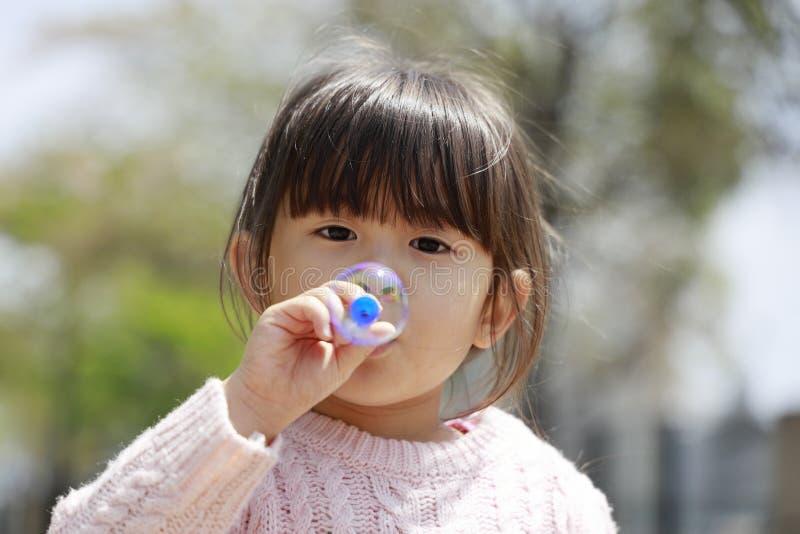 Ιαπωνικό παιχνίδι κοριτσιών με τη φυσαλίδα κάτω από το μπλε ουρανό στοκ φωτογραφία