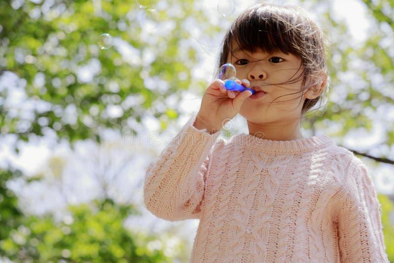 Ιαπωνικό παιχνίδι κοριτσιών με τη φυσαλίδα κάτω από το μπλε ουρανό στοκ εικόνα