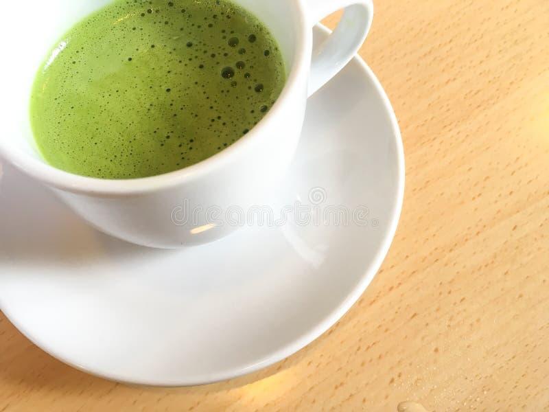 Ιαπωνικό πράσινο τσάι matcha latte σε ένα άσπρο φλυτζάνι και ένα άσπρο πιατάκι στοκ φωτογραφία με δικαίωμα ελεύθερης χρήσης