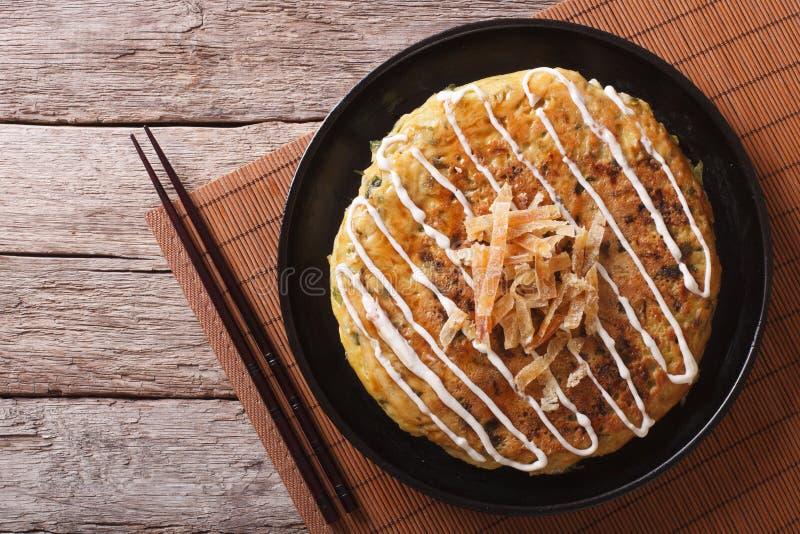 Ιαπωνικό okonomiyaki σε έναν ξύλινο πίνακα οριζόντια τοπ άποψη στοκ φωτογραφίες