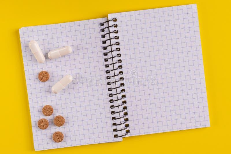 Ιατρικά κάψες και χάπια γύρω από ένα κενό σημειωματάριο σε ένα κίτρινο υπόβαθρο, κινηματογράφηση σε πρώτο πλάνο στοκ φωτογραφίες με δικαίωμα ελεύθερης χρήσης
