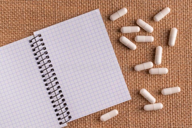Ιατρικά κάψες και χάπια γύρω από ένα κενό σημειωματάριο σε ένα ψάθινο υπόβαθρο, κινηματογράφηση σε πρώτο πλάνο στοκ φωτογραφία με δικαίωμα ελεύθερης χρήσης