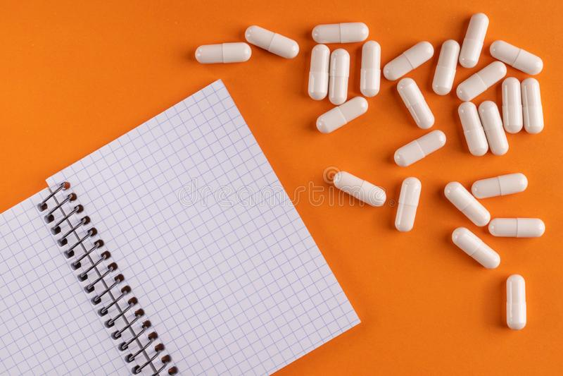 Ιατρικά κάψες και χάπια ιατρικής γύρω από ένα κενό σημειωματάριο σε ένα πορτοκαλί υπόβαθρο, κινηματογράφηση σε πρώτο πλάνο στοκ εικόνες