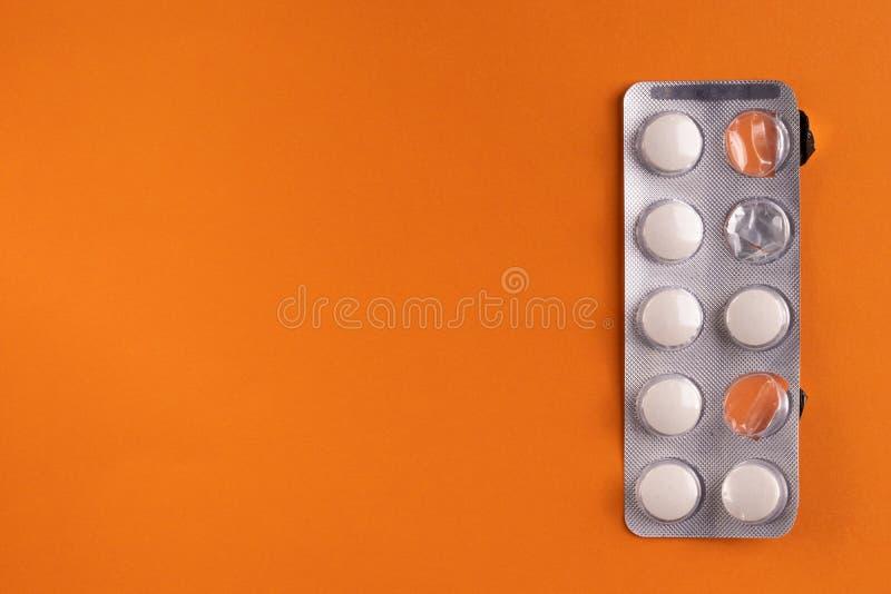 Ιατρικά κάψες και χάπια σε ένα πορτοκαλί υπόβαθρο, κινηματογράφηση σε πρώτο πλάνο στοκ εικόνες