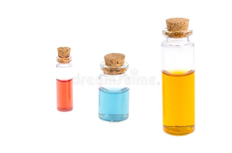 Ιατρικά μπουκάλια γυαλιού με το χρωματισμένο υγρό που απομονώνεται στο λευκό στοκ φωτογραφία