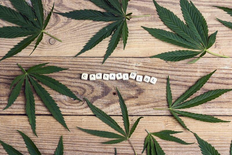Ιατρικά φύλλα καννάβεων με τη λέξη Cannabidiol στην παλαιά ξύλινη πλάτη στοκ εικόνα με δικαίωμα ελεύθερης χρήσης