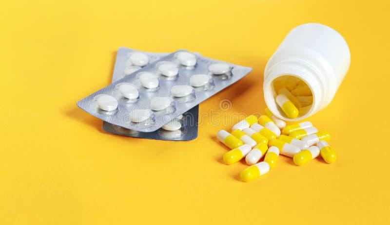 Ιατρικά χάπια με ένα μπουκάλι στο κίτρινο υπόβαθρο στοκ φωτογραφία με δικαίωμα ελεύθερης χρήσης