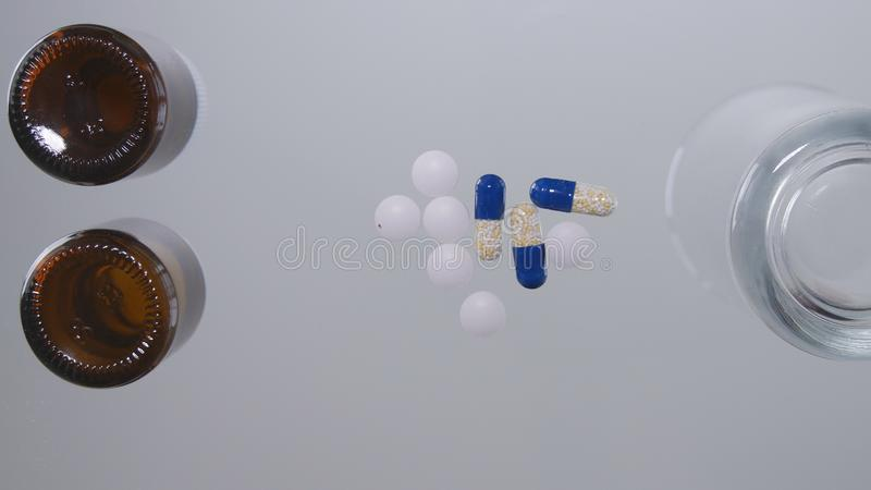 Ιατρικά χάπια παραληπτών και ένα γυαλί με το νερό στην επιτραπέζια επιφάνεια στοκ εικόνες