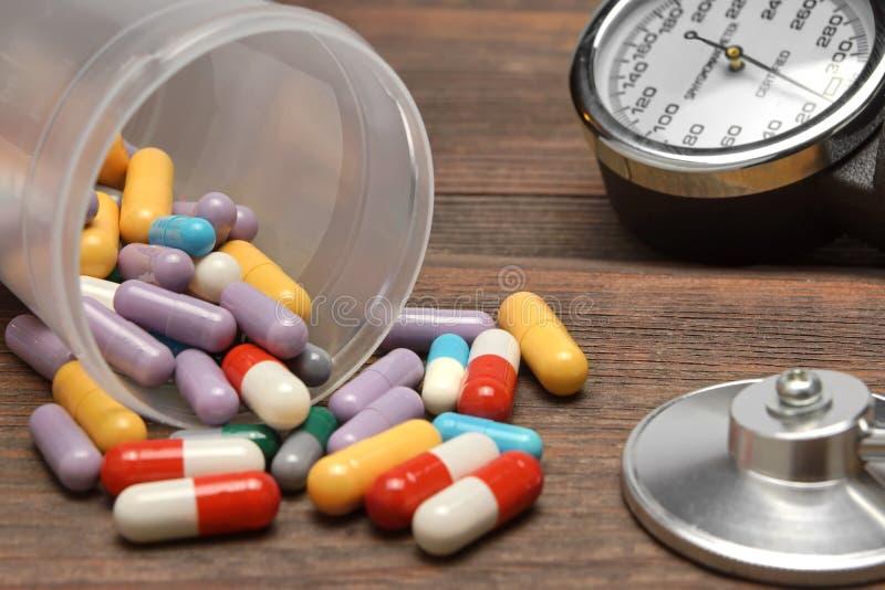 Ιατρικές συσκευές και διεσπαρμένος από τα χάπια φιαλιδίων στον ξύλινο πίνακα στοκ φωτογραφία με δικαίωμα ελεύθερης χρήσης