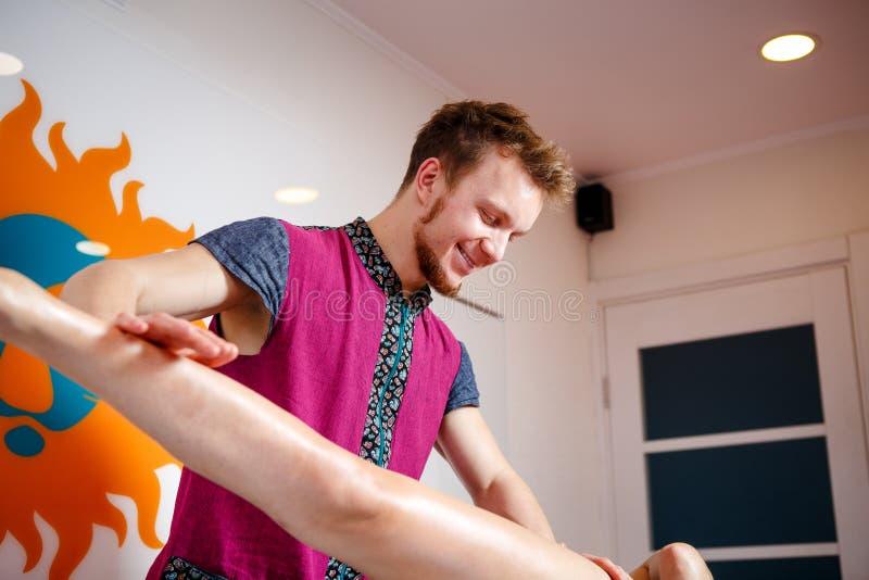 Ιατρική και αποκατάσταση θέματος Ο νέος αρσενικός μασέρ γιατρών μεταχειρίζεται να τρίψει τα πόδια μιας νέας γυναίκας σε έναν πίνα στοκ εικόνες