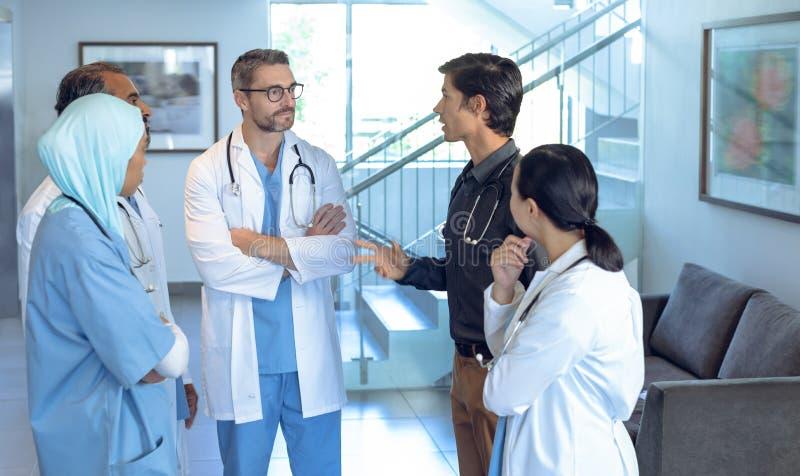 Ιατρική ομάδα των γιατρών που μιλούν ο ένας με τον άλλον στο λόμπι στοκ εικόνες
