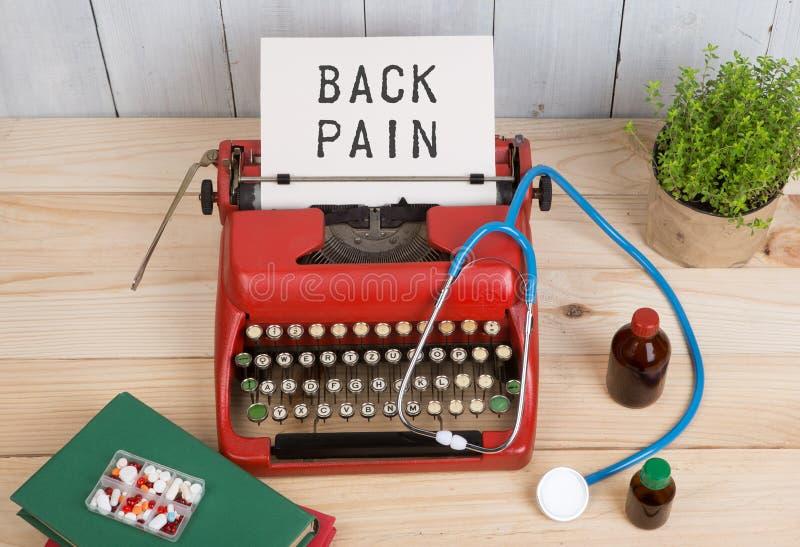 Ιατρική συνταγών ή ιατρική διάγνωση - εργασιακός χώρος γιατρών με το στηθοσκόπιο, χάπια, γραφομηχανή με τον πόνο στην πλάτη κειμέ στοκ φωτογραφία με δικαίωμα ελεύθερης χρήσης