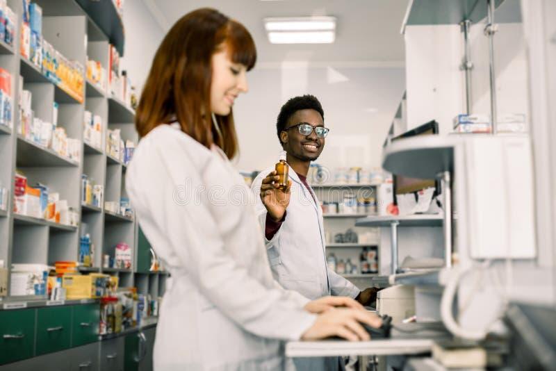 Ιατρική, φαρμακευτικά προϊόντα, υγειονομική περίθαλψη και έννοια ανθρώπων - ευτυχής αφρικανικός φαρμακοποιός ατόμων που παρουσιάζ στοκ εικόνα