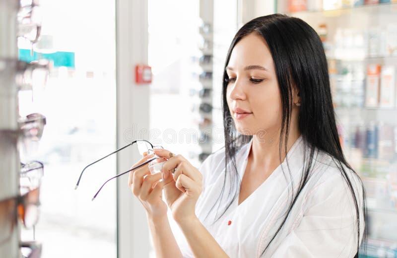 Ιατρική, φαρμακευτική και οπτική Μια νεαρή γυναίκα με λευκή ρόμπα κρατά ένα ζευγάρι γυαλιά και μελετά την ετικέτα Κλείσιμο στοκ εικόνα με δικαίωμα ελεύθερης χρήσης
