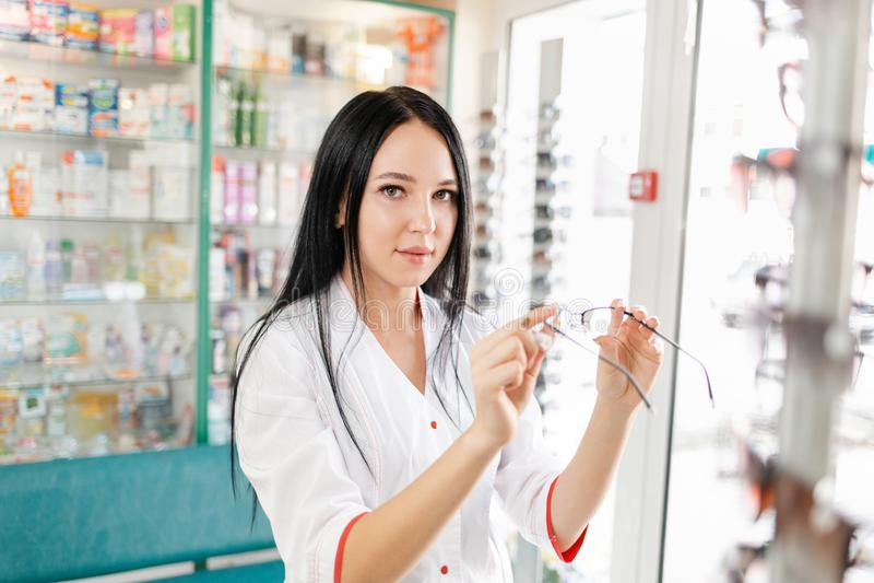 Ιατρική, φαρμακευτική και οπτική Μια νεαρή μελαχρινή γυναίκα με λευκό παλτό που κρατά γυαλιά όρασης στοκ φωτογραφίες με δικαίωμα ελεύθερης χρήσης