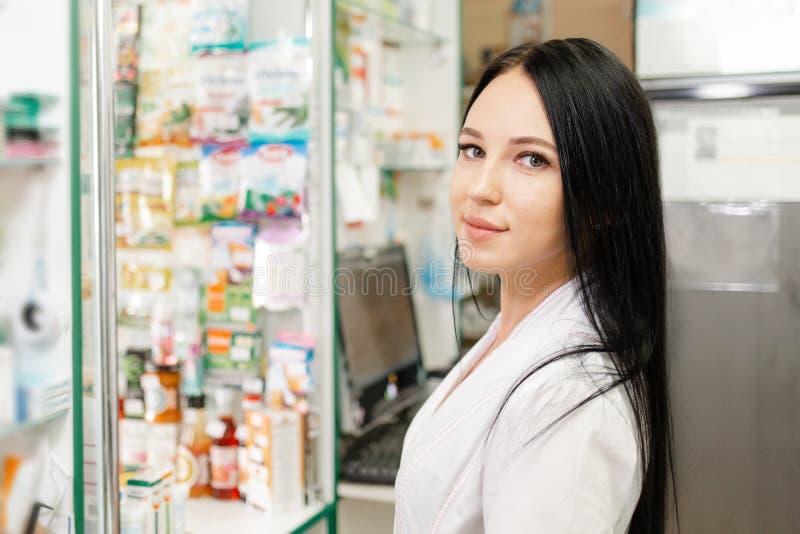 Ιατρική, φαρμακευτική και οπτική Πορτρέτο γυναίκας γιατρού ή φαρμακοποιού με λευκό παλτό, που δείχνει με χαμόγελο Στο φόντο στοκ φωτογραφία με δικαίωμα ελεύθερης χρήσης