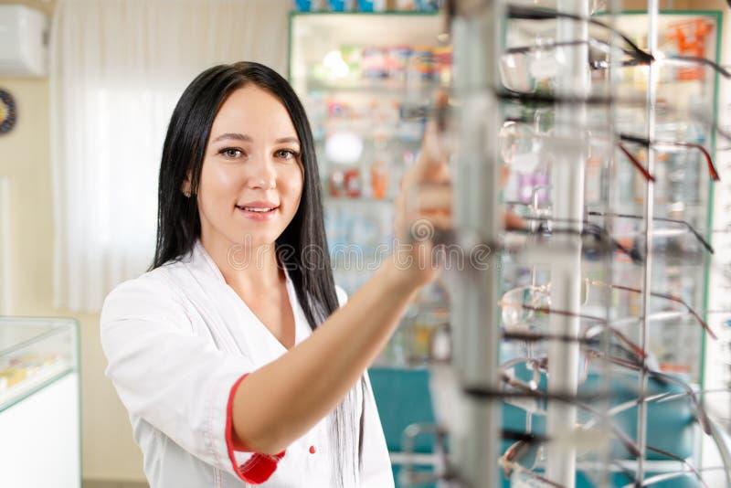 Ιατρική, φαρμακευτική και οπτική Πορτρέτο μιας γυναίκας γιατρού ή φαρμακοποιού με λευκό παλτό, που κοιτάζει με χαμόγελο και τραβά στοκ εικόνες