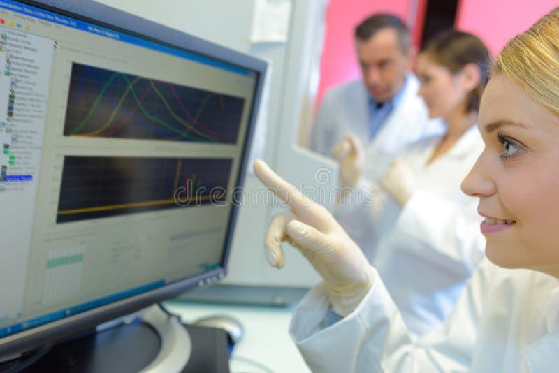Ιατρικοί επιστήμονες που χρησιμοποιούν τα ψηφιακά μηχανήματα στο εργαστήριο στοκ εικόνες