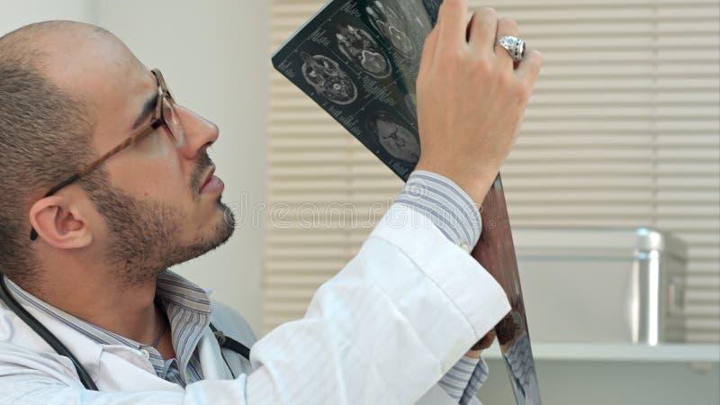 Ιατρικός εργαζόμενος που αναλύει υπολογισμένη την εγκέφαλος των ακτίνων X εικόνα τομογραφίας στοκ φωτογραφία
