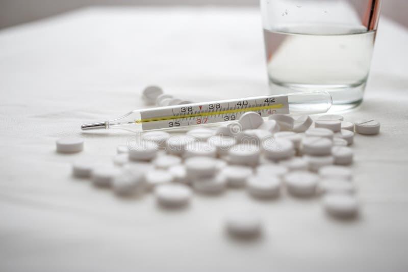 Ιατρικό θερμόμετρο και στα επιτραπέζια άσπρα χάπια και το ποτήρι του νερού στοκ φωτογραφίες