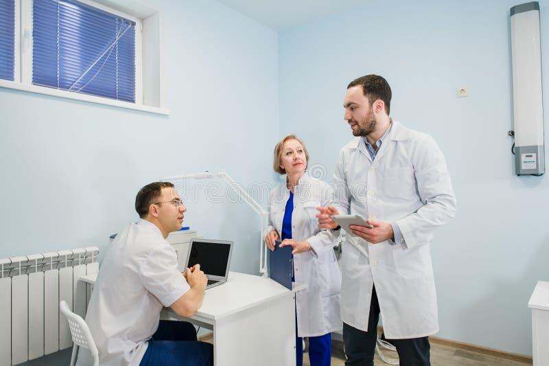 Ιατρικό προσωπικό που συζητά πέρα από τις ιατρικές εκθέσεις που χρησιμοποιούν το PC lap-top και ταμπλετών Επαγγελματίες υγειονομι στοκ εικόνες
