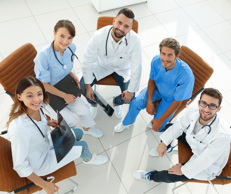Ιατρικό προσωπικό που συζητά τα τρέχοντα ζητήματα, που κάθονται πίσω από ένα γραφείο στοκ εικόνες
