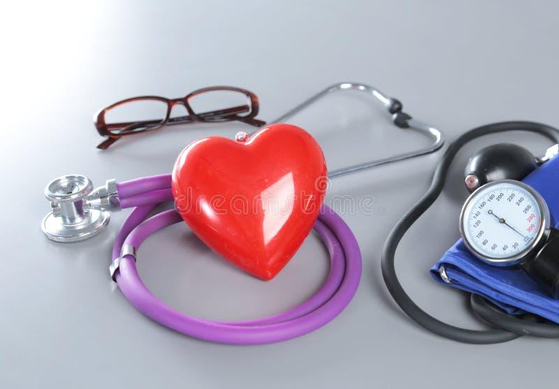 Ιατρικό στηθοσκόπιο και κόκκινη καρδιά που απομονώνονται στο λευκό στοκ εικόνα