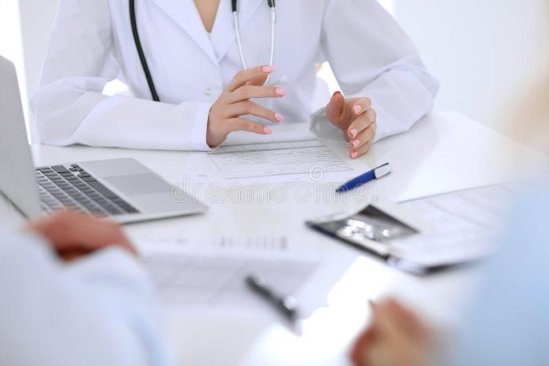 Ιατρός και νέοι ασθενείς ζευγών που συζητούν κάτι στον πίνακα Κινηματογράφηση σε πρώτο πλάνο χεριών στοκ εικόνα με δικαίωμα ελεύθερης χρήσης