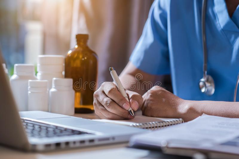 Ιατρός που κάθεται στο τραπέζι και γράφει σε έκθεση εγγράφων στο νοσοκομειακό γραφείο στοκ εικόνες